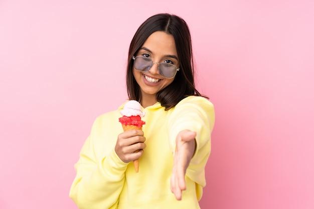 Jeune fille brune tenant une glace au cornet sur un mur rose isolé se serrant la main pour fermer une bonne affaire
