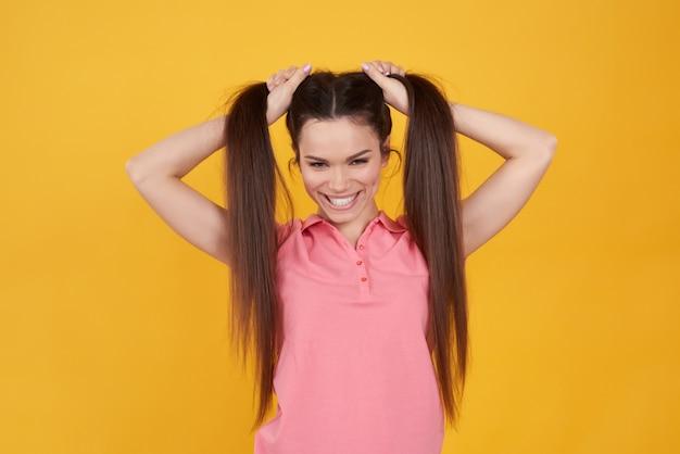 Jeune fille brune tenant joyeusement les cheveux isolés.