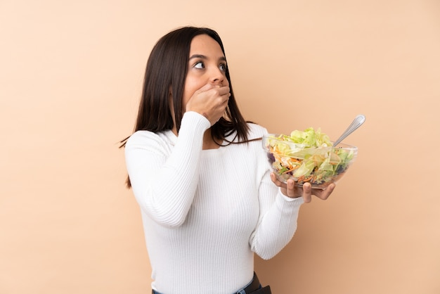 Jeune fille brune tenant une salade sur fond isolé couvrant la bouche et regardant sur le côté
