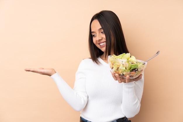 Jeune fille brune tenant une salade sur fond isolé sur fond imaginaire sur la paume pour insérer une annonce