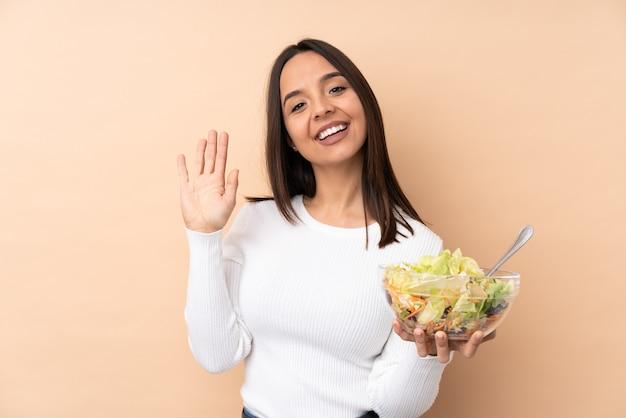 Jeune fille brune tenant une salade sur fond isolé saluant avec la main avec une expression heureuse