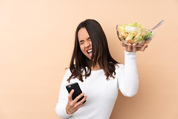 Jeune fille brune tenant une salade sur fond isolé avec téléphone en position de victoire