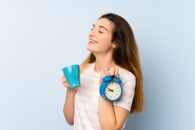 Jeune fille brune tenant une tasse de café et une horloge vintage