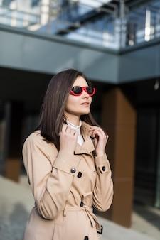 Jeune fille brune en vêtements décontractés se promener dans le centre-ville pendant la journée