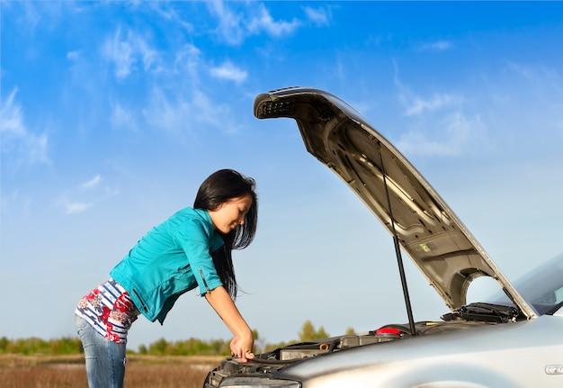 Jeune fille brune avec une voiture cassée avec capot ouvert