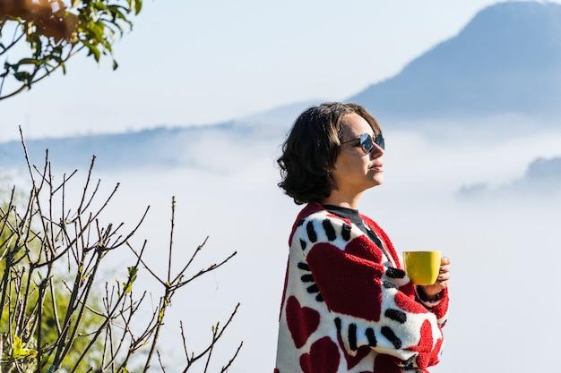 Jeune fille buvant du café dans une tasse par temps froid trop de brouillard et de nuages couvrent la vue sur la ville