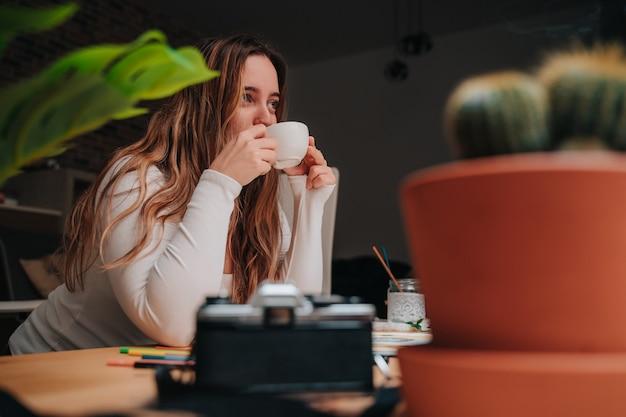 Une jeune fille buvant du café sur une table en bois. elle a des pinceaux, de l'encens, des appareils photo et une grande fenêtre.