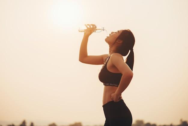 Jeune fille buvant de l'eau pendant le jogging