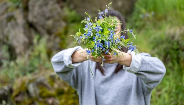 La jeune fille cache son visage derrière un bouquet de fleurs fraîches recueillies dans la forêt