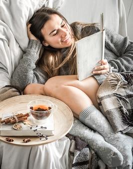 La jeune fille sur le canapé avec du thé et un livre