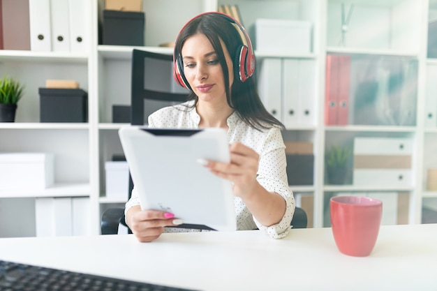 Une jeune fille avec un casque assis dans le bureau à la table d'ordinateur et tenant une tablette.