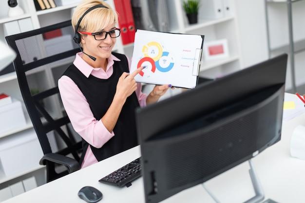 Une jeune fille avec un casque assis à une table d'ordinateur et tenant une feuille dans un diagramme.
