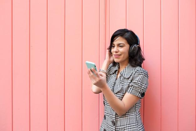 Jeune fille avec un casque en regardant comme elle sourit à son téléphone portable