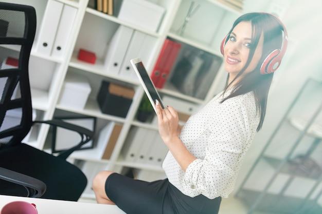Une jeune fille avec un casque s'assit sur la table et tenait une tablette.