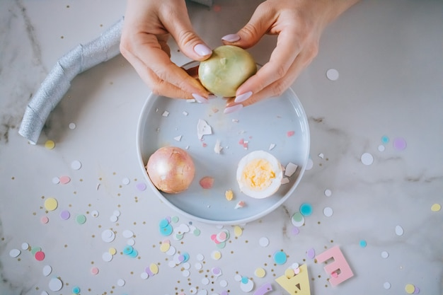 Jeune fille casse des oeufs de pâques sur fond de marbre, des confettis, des étincelles, des rubans.