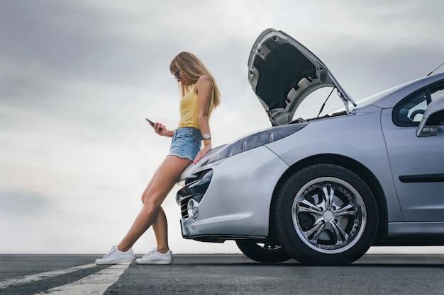 La jeune fille a cassé la voiture et elle a ouvert le capot et a essayé de réparer la voiture sur la route. une femme appelle sur un smartphone avec un service d'évacuation de voiture.