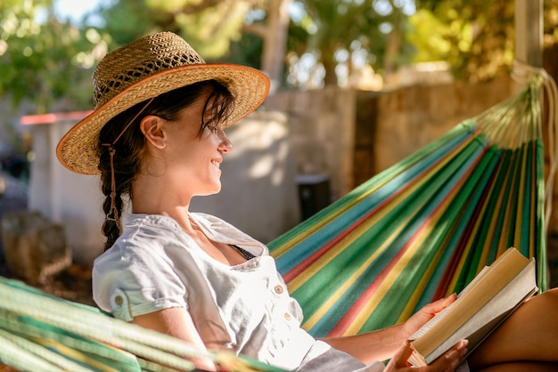 Jeune fille caucasienne assise sur un hamac dans un jardin lit un livre