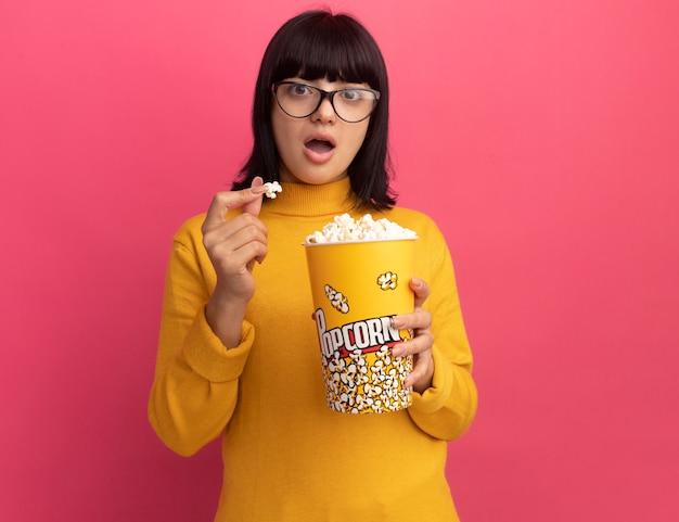 Une jeune fille caucasienne brune excitée dans des lunettes optiques tient un seau de pop-corn isolé sur un mur rose avec un espace de copie