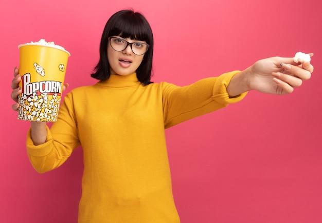 Une jeune fille caucasienne brune impressionnée dans des lunettes optiques tient un seau à pop-corn et pointe sur le côté