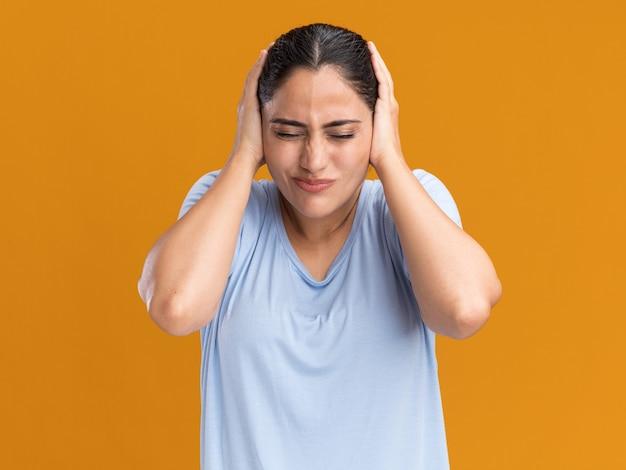 Une jeune fille caucasienne brune mécontente couvre les oreilles avec les mains isolées sur le mur orange avec espace de copie