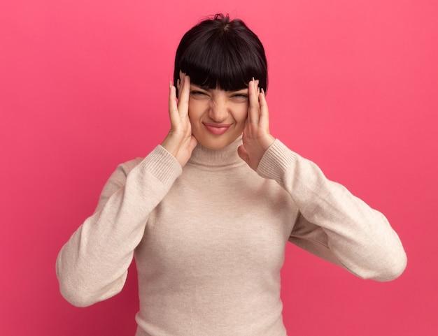 Une jeune fille caucasienne brune mécontente met les mains sur les temples isolés sur un mur rose avec espace pour copie