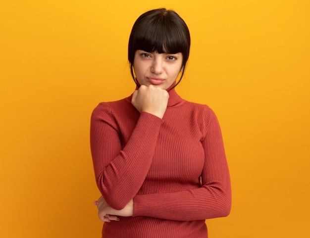 Une jeune fille caucasienne brune mécontente met le poing sur le menton et isolée sur un mur orange avec espace de copie
