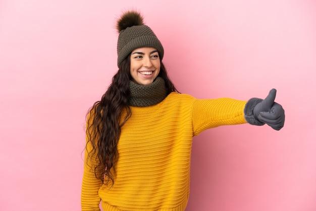 Jeune fille caucasienne avec chapeau d'hiver isolé sur mur violet donnant un geste de pouce en l'air