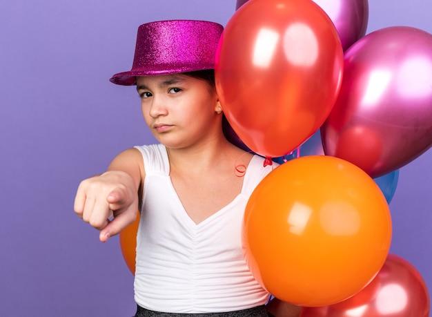 Jeune fille caucasienne confiante avec un chapeau de fête violet tenant des ballons à l'hélium et pointant isolé sur un mur violet avec espace de copie