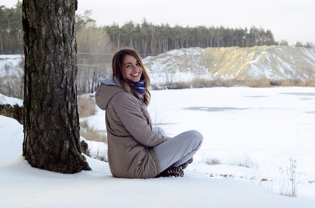 Une jeune fille caucasienne dans un manteau brun est assise près d'une falaise. ligne d'horizon entre le ciel et un lac gelé en hiver