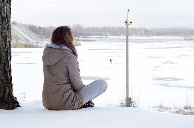 Une jeune fille caucasienne dans un manteau brun regardant au loin sur la ligne d'horizon entre le ciel et le lac gelé en hiver