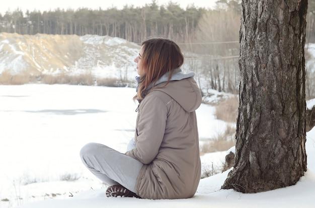Une jeune fille caucasienne dans un manteau marron regardant au loin sur la ligne d'horizon