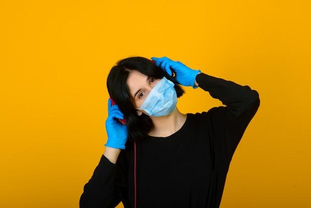 La jeune fille caucasienne dans un masque de protection de couleur bleue. portrait tourné sur fond jaune.