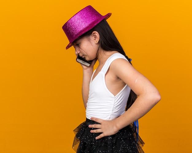Jeune fille caucasienne déçue avec un chapeau de fête violet parlant au téléphone isolé sur un mur orange avec espace de copie