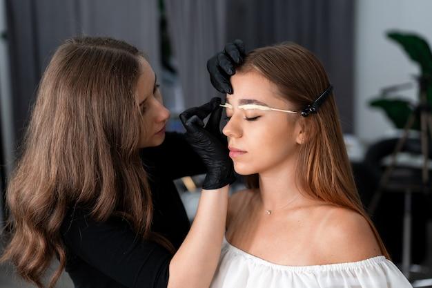 Jeune fille caucasienne esthéticienne détient modèle correction des sourcils esthéticienne au travail est le lieu de travail d'un spécialiste des sourcils. procédure de correction et de teinture des sourcils. l'industrie de la beauté. mode de vie