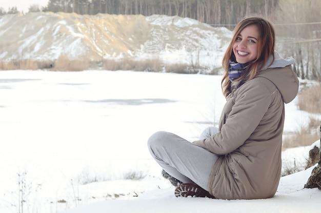 Une jeune fille caucasienne en habit brun est assise près d'une falaise à l'arrière-plan d'une ligne d'horizon