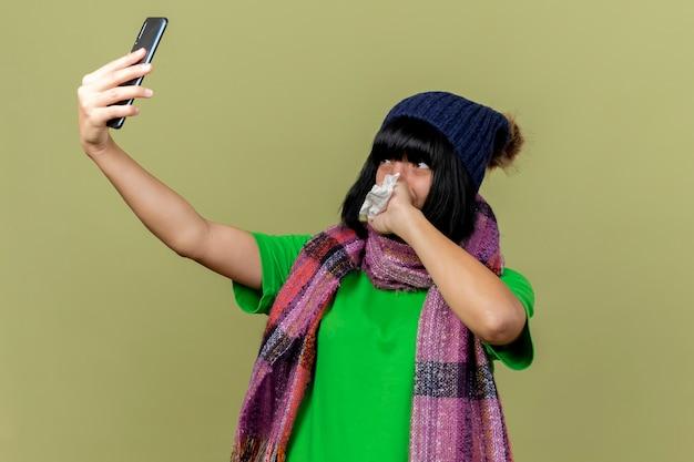 Jeune fille caucasienne malade portant un chapeau d'hiver et une écharpe prenant selfie tenant une serviette en gardant la main sur la bouche isolée sur fond vert olive avec espace copie