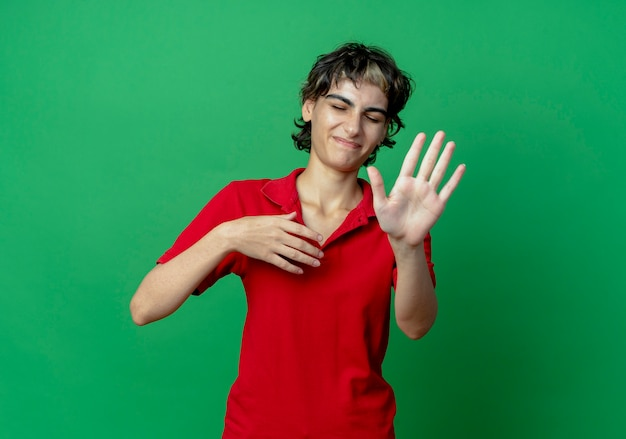 Jeune fille caucasienne mécontente avec une coupe de cheveux de lutin gardant la main en l'air et faisant des gestes non les yeux fermés