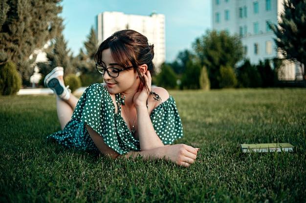 Jeune fille caucasienne en robe rétro vintage lit un livre sur la pelouse pendant le coucher du soleil