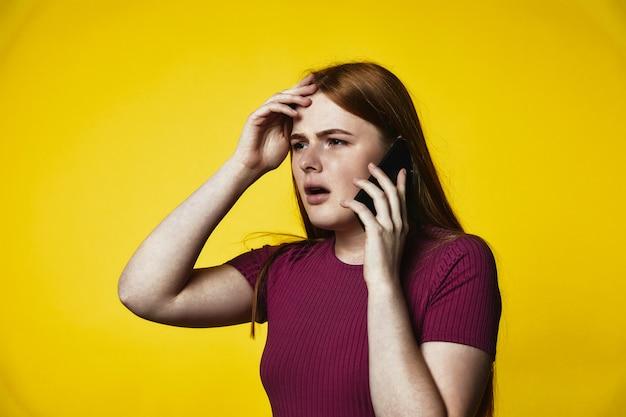 Jeune fille caucasienne rousse bouleversée parle au téléphone portable