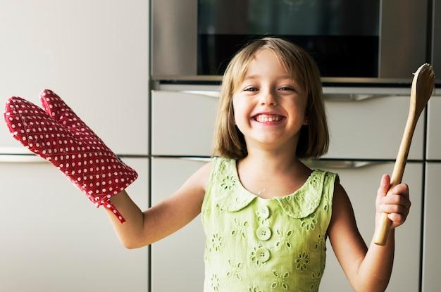 Jeune fille caucasienne souriante avec des ustensiles de cuisson
