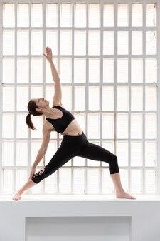 Jeune fille caucasienne en tenue de sport noire, faire des exercices de yoga à côté d'une grande fenêtre dans son studio. espace pour le texte.