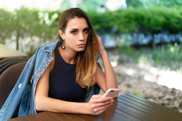 Une jeune fille caucasienne triste, assise dans un café d'été ouvert avec un téléphone