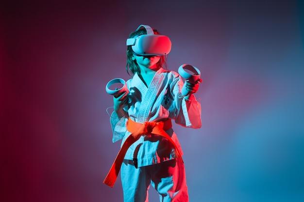 Jeune fille caucasienne en uniforme de karaté jouant à des jeux vidéo avec réalité virtuelle