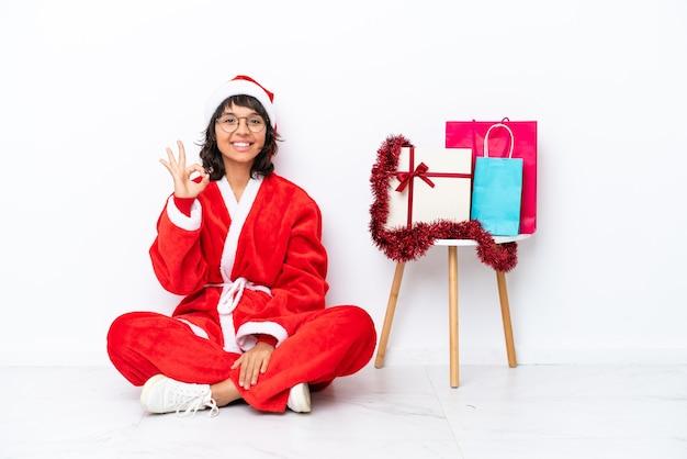 Jeune fille célébrant noël assis sur le sol isolé sur blanc bakcground montrant un signe ok avec les doigts