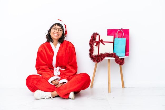 Jeune fille célébrant noël assis sur le sol isolé sur blanc bakcground posant avec les bras à la hanche et souriant