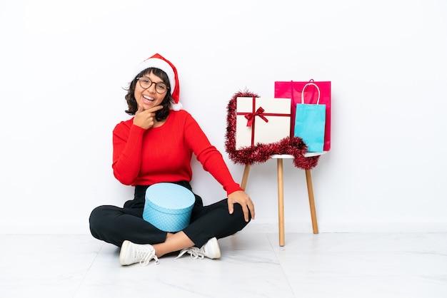 Jeune fille célébrant noël assis sur le sol isolé sur fond blanc avec des lunettes et souriant