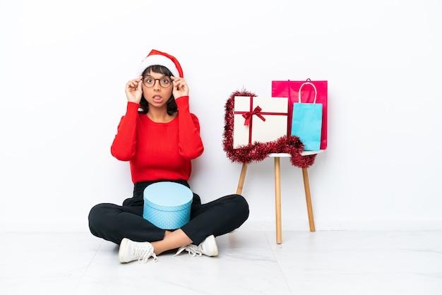 Jeune fille célébrant noël assis sur le sol isolé sur fond blanc avec des lunettes et surpris