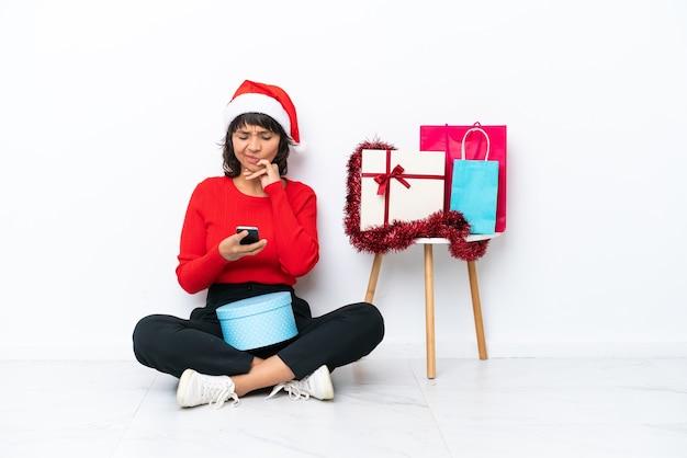 Jeune fille célébrant noël assise sur le sol isolé sur fond blanc pensant et envoyant un message