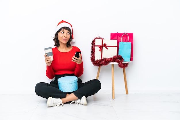 Jeune fille célébrant noël assise sur le sol isolée sur fond blanc tenant du café à emporter et un mobile tout en pensant à quelque chose