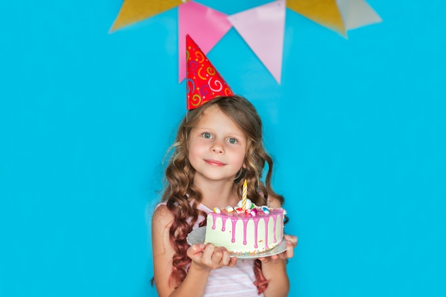 Jeune fille célébrant tenant un morceau de gâteau sur fond bleu. espace copie